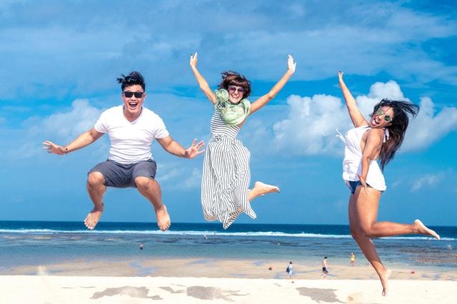Usmiati ľudia, ktorí skáču na pláži