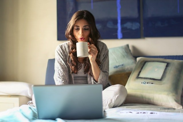 Žena sediaca na posteli s notebookom, ktorá pije kávu.jpg