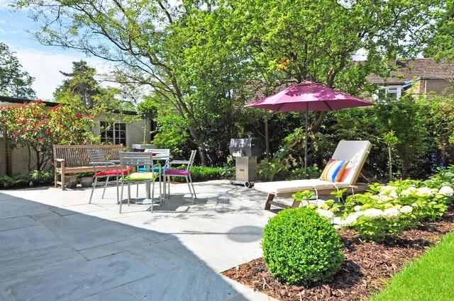 Záhrada s malým domčekom, ležadlami, slnečníkom a záhradným nábytkom